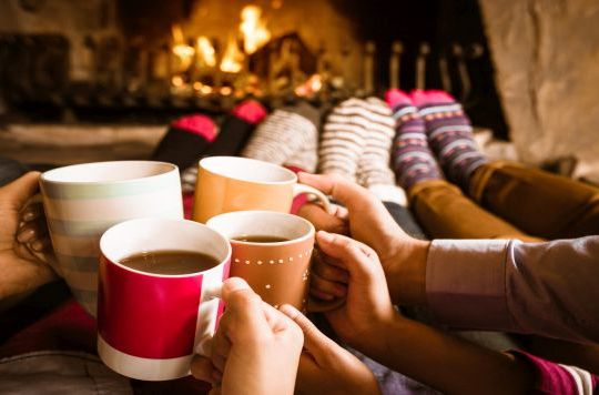 Four people warming their feet by the fireplace and drinking hot chocolate.